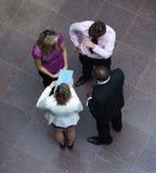 Alto ángulo de los hombres de negocios que hablan en oficina Foto de archivo