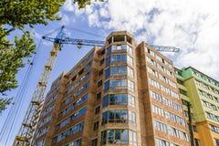 Alto piano moderno che costruisce in costruzione con la gru a torre Fotografia Stock Libera da Diritti