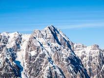 Alto picco nevoso roccioso il giorno di inverno soleggiato con cielo blu Cresta alpina della montagna Fotografie Stock Libere da Diritti