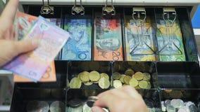 Alto punto di vista di un commesso che prende valuta australiana da un registratore di cassa stock footage