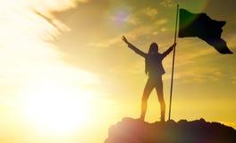 Alto risultato, siluette della ragazza, bandiera della vittoria sulla cima Fotografie Stock Libere da Diritti