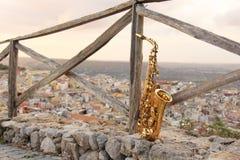 Alto Saxophone de oro en el fondo de la naturaleza y de la ciudad imagenes de archivo