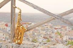 Alto Saxophone de oro en el fondo de la naturaleza y de la ciudad foto de archivo