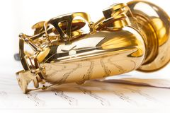 Alto saxophone with detailed view from bow part. Shiny golden alto saxophone with detailed view from bow part on the musical notes background with standard Royalty Free Stock Images