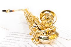 Alto saxophone laying on the musical notes Stock Photo