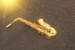 Alto Saxophone Lies de oro en el fondo negro Romántico y imágenes de archivo libres de regalías