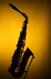 Alto Saxophone in Silhouette on Yellow Royalty Free Stock Image
