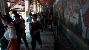Alto stupa de oro y turistas que caminan en Wat Phra Kaew almacen de video