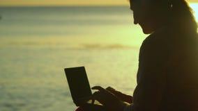 Alto vicino del computer portatile Le toppe solari di luce di un declino sono riflesse nelle onde del mare Le stampe della donna  stock footage