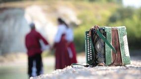 Alto vicino della fisarmonica, sui precedenti di un gruppo di giovani in costumi rossi nazionali russi archivi video