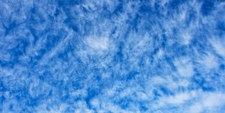 Altocumulus cloudscape texture. On bright blue sky Stock Images
