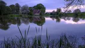 Reflections of St Leonard's church in Hartley Mauditt Pond, South Downs National Park, UK stock photo