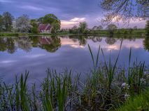 Reflections of St Leonard's church in Hartley Mauditt Pond, South Downs National Park, UK stock photos