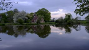 Reflections of St Leonard`s church in Hartley Mauditt Pond, South Downs National Park, UK stock photos