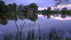 Reflections of St Leonard`s church in Hartley Mauditt Pond, South Downs National Park, UK stock photo