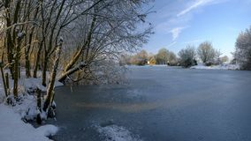 Frozen winter scene over Hartley Mauditt pond to St Leonard`s Church, South Downs National Park, Hampshire, UK royalty free stock photography