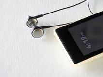 Altoparlante della spina dell'orecchio e del telefono cellulare su bianco Fotografia Stock Libera da Diritti