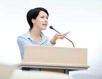 Altoparlante grazioso della donna al podio Immagini Stock