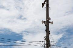 Altoparlanti sul palo elettrico con un fondo del cielo blu Fotografia Stock