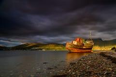 Altopiani del paesaggio della Scozia, della barca abbandonata del pescatore e di Ben Nevis al tramonto immagine stock