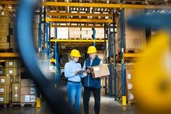 Altos directivos o supervisores con la tableta que trabaja en un almacén, acción que controla Imagenes de archivo