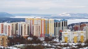 Altos edificios coloreados brillantes en el fondo de colinas nevadas y río en día de invierno metrajes