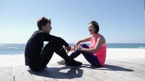 Altos fives felices del hombre joven y de la mujer que se sientan cerca de la playa Ondas que salpican agains las rocas Alto jove almacen de video