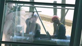 Altos trabajadores valientes de la subida que limpian el vidrio de la ventana, comercio peligroso, riesgo a la salud almacen de video