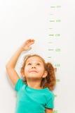 Altura de la medida de la muchacha con la mano que mira para arriba foto de archivo