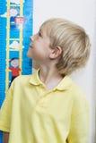 Altura de medição do menino na sala de aula Foto de Stock Royalty Free