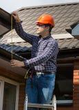 Altura de medición del trabajador profesional del tejado con la cinta Imagen de archivo libre de regalías