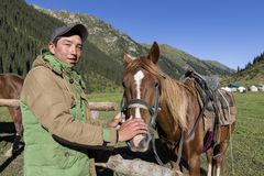 Altyn-Arashan, Kirguistán, el 14 de agosto de 2018: Un kirguizio joven frota ligeramente cariñosamente un caballo en el valle de  imágenes de archivo libres de regalías
