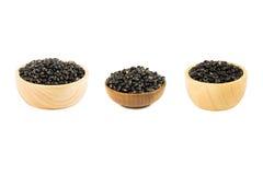 Alubias negras de la semilla en la taza de madera en blanco Imagenes de archivo
