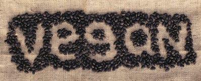 Alubias negras que forman al vegano de la palabra Foto de archivo