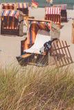 Alugue a cadeira telhada vermelha no Sandy Beach em Travemunde, Alemanha norte Grama seca no primeiro plano fotografia de stock