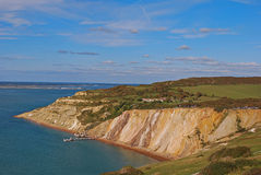 Alum Bay with her popular coloured sand with pier and chairlift station. Surrounded by endless green fields. It is a bay nearby the western most point of the Stock Photography
