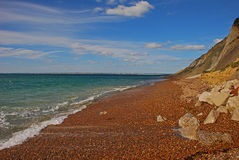 Alum Bay with red pebbles sand in Isle of Wight. Alum Bay with red pebbles sand and rocky beach at Isle of Wight during sunny warm weather in summer Stock Photography