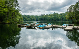 Aluminium bass fishing boat and pedalos. At wooden dock in Virginia, America USA royalty free stock images