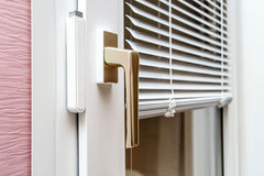 Aluminium blinds on PVC window. Aluminium blinds on new plastic window with handle Stock Images