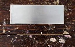 Aluminium borstade plattan på trä med fläcken av färger Arkivfoton