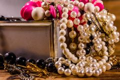 Aluminium case full of different jewelry on wooden table royalty free stock images