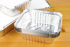 Aluminium Foil Take Away Food Containers. Aluminium foil take away trays on a wooden background Royalty Free Stock Photo