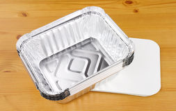 Aluminium Foil Take Away Food Containers. Aluminium foil take away trays on a wooden background Stock Photos