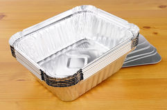 Aluminium Foil Take Away Food Containers. Aluminium foil take away trays on a wooden background royalty free stock photography