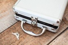 Aluminium geopende koffer met sleutels op vloer Stock Fotografie
