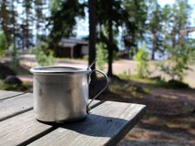 Aluminium mug for camping on a wooden table in a campsite in Finland. Aluminium mug for camping with a spoon in it on a wooden table in a campsite in Finland stock image