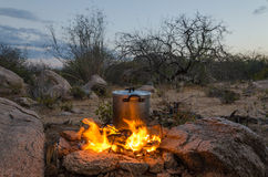 Aluminium pot being heated over outdoor camp fire. Aluminium pot standing on foldable grill being heated over outdoor camp fire surrounded by rocks Royalty Free Stock Photography