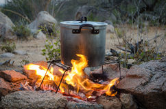 Aluminium pot being heated over outdoor camp fire Royalty Free Stock Photo
