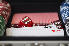 Aluminium suitcase with poker set, cards, red dice and two aces Royalty Free Stock Photos