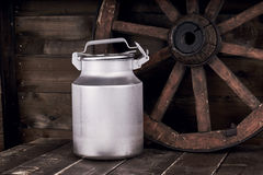 Aluminium water can and old wheel Royalty Free Stock Images